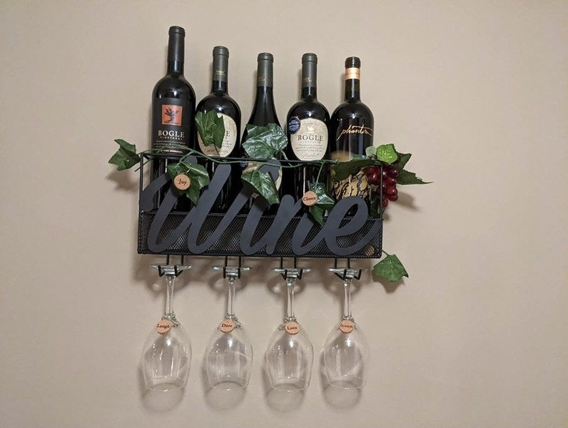 """A metal wine container that reads """"wine"""" mounted on a wall with clear wine glasses and faux ivy"""