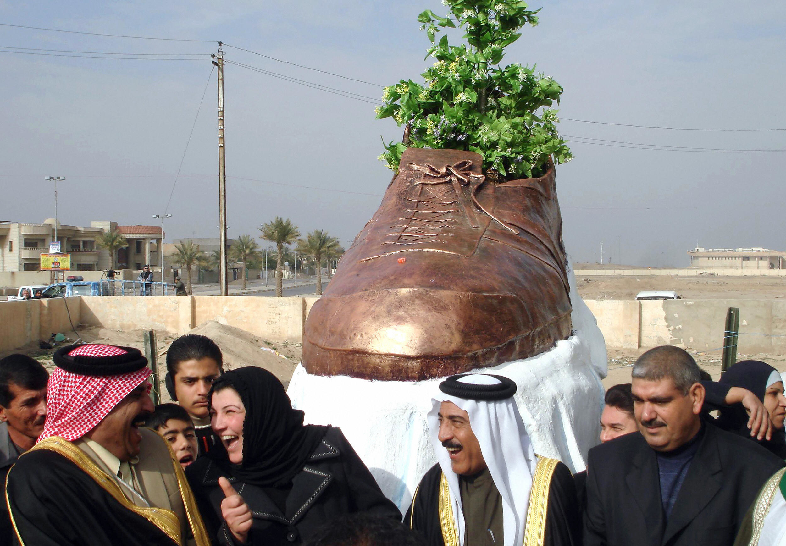 A large bronze shoe with a plant growing out of it