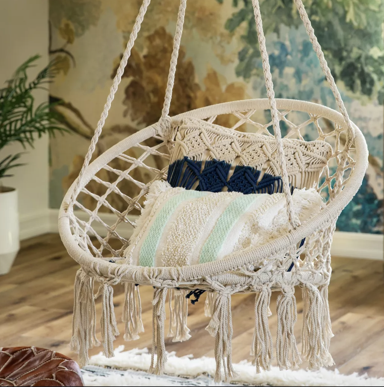 The white woven macrame seat is in a circular shape with a blue throw pillow