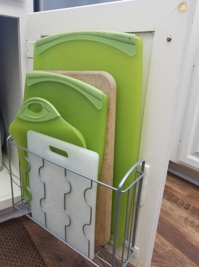 A silver over the wall organizer mounted on a cabinet door holding cutting boards
