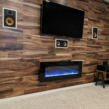 reviewer's electric fireplace mounted underneath a television