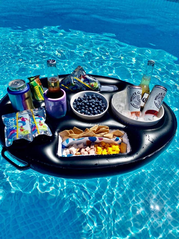 Reviewer black round inflatable holding a bucket of ice and three alcoholic drinks, snacks, cans of soda, Capri Suns, and more