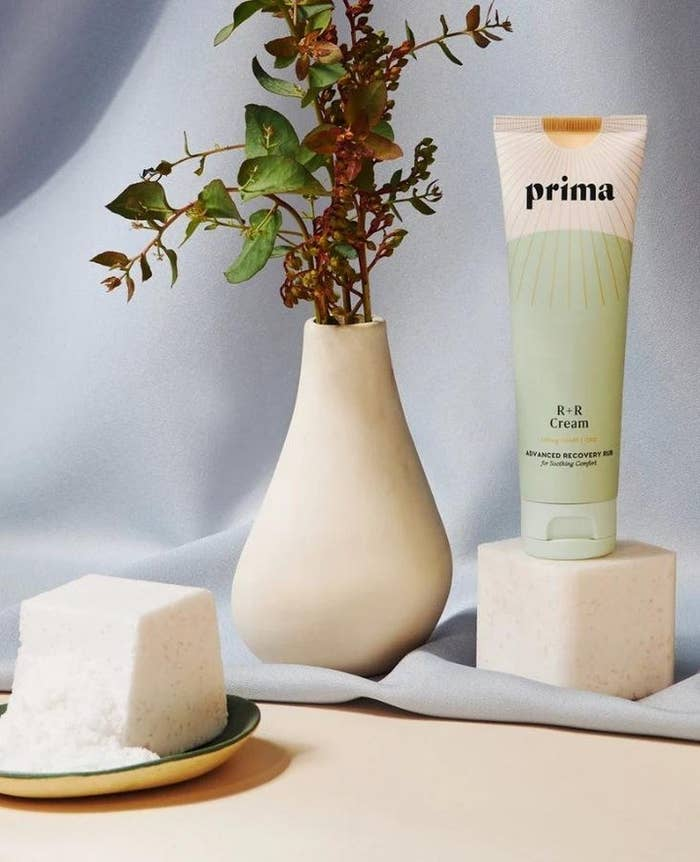 a product shot of the cream on top of a stone block next to a vase and we can see the size of the bottle which appears to be small but larger than mini size