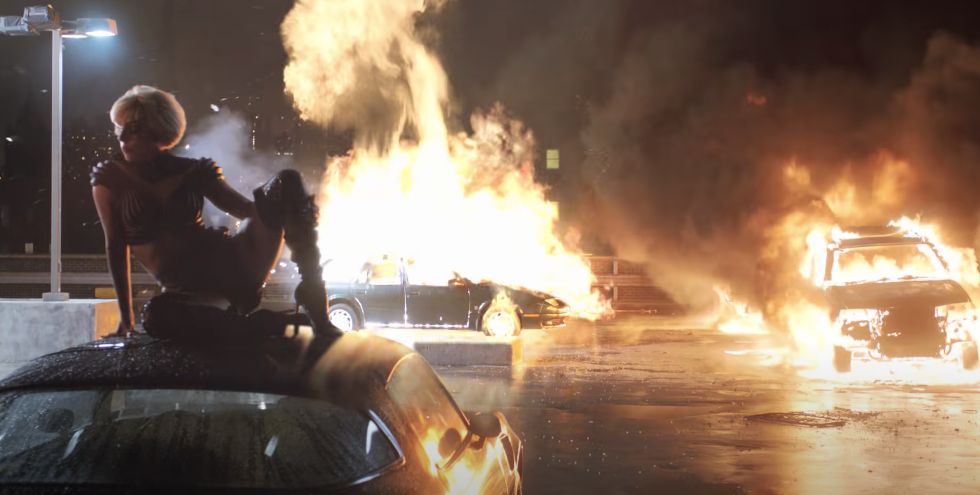 Gaga sitting on top of a car while others explode around her in the Marry The Night music video