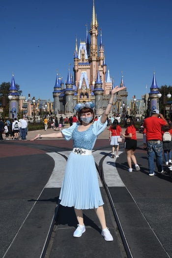 another reviewer in the skirt in light blue in front of cinderella's castle