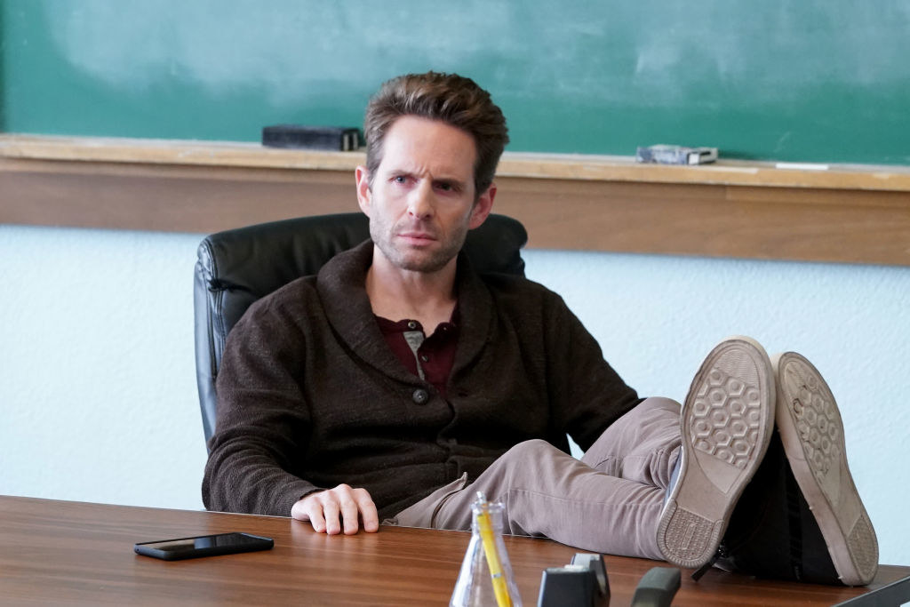 Glenn Howerton as Jack sitting at his desk with his feet up