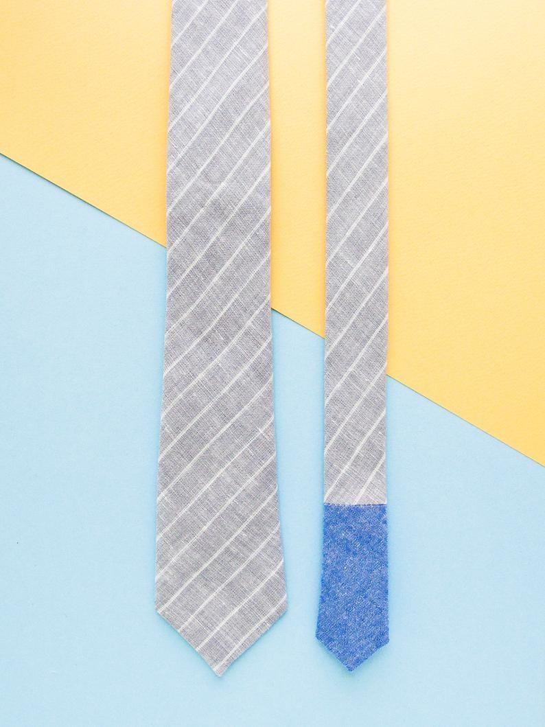 grey neck tie with diagonal white stripes and blue tip