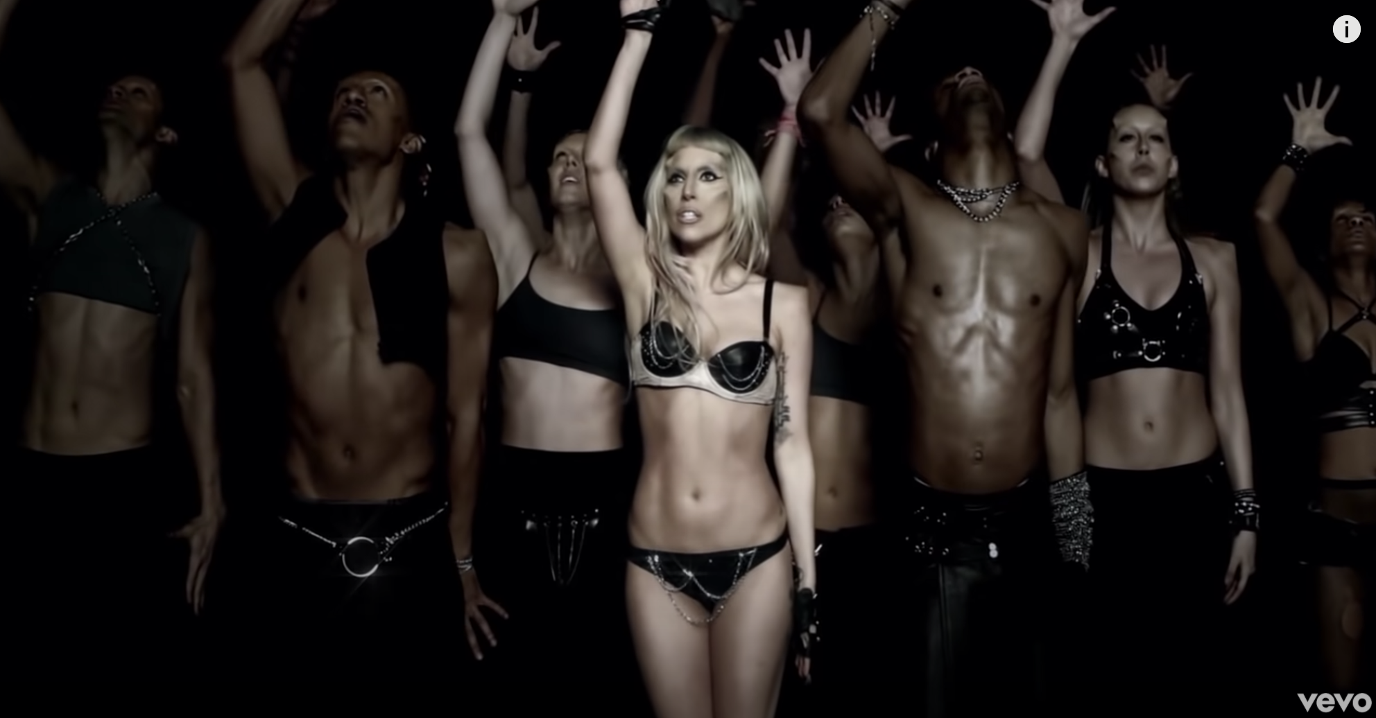 Gaga holding her hand up with her dancers in the Born This Way music video