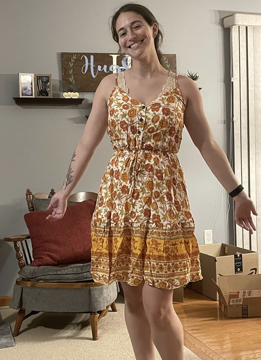 reviewer wearing the dress that has spaghetti straps, buttons, and an orange and yellow pattern