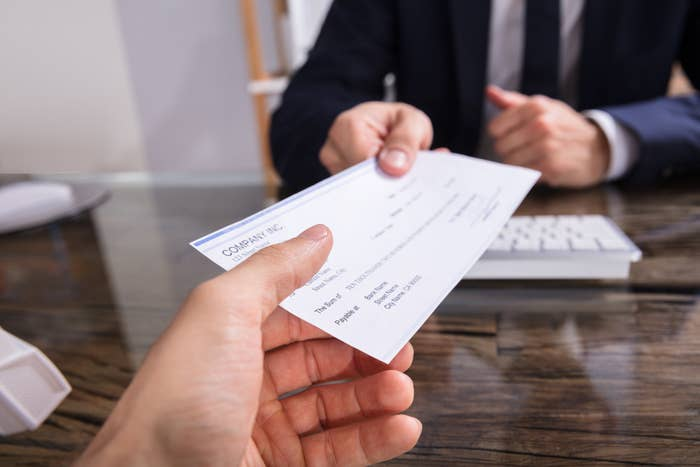 Businessperson giving a cheque to colleague