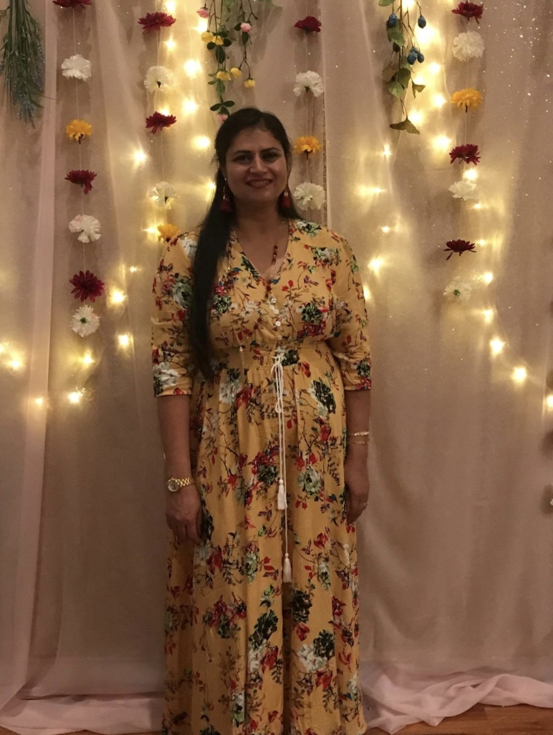 reviewer wearing the maxi dress with button and tassel details and 3/4 sleeves in yellow floral
