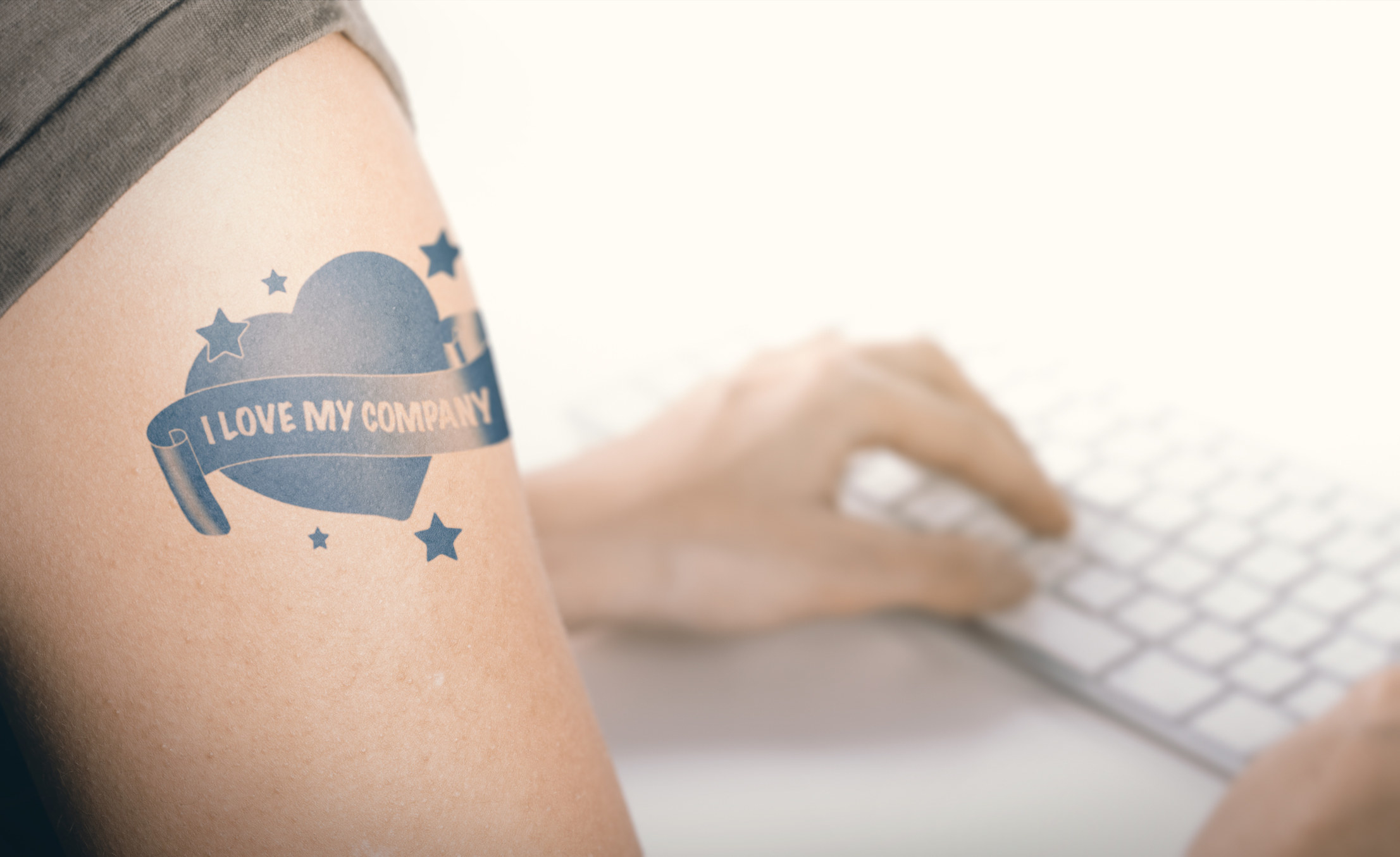 Woman working on a computer with close up on a tattoo with the text i love my company on her arm
