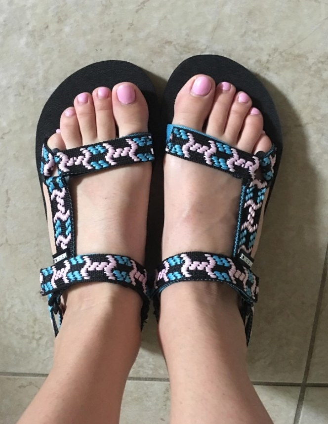 A reviewer wearing the sandals in a multicolored pattern