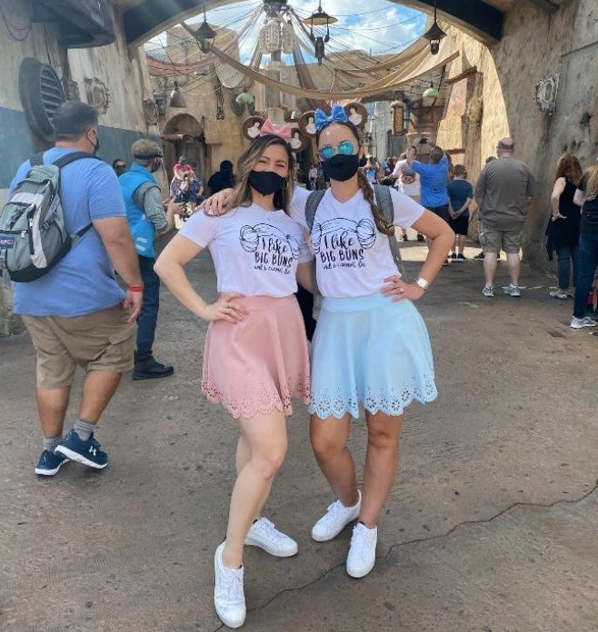a reviewer and their sister wearing the skirts in pink and blue