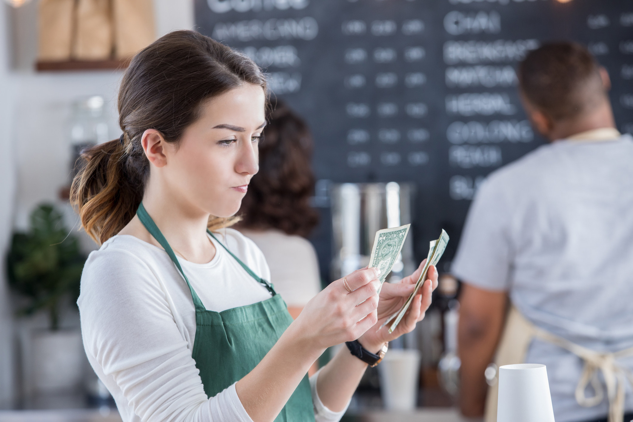 Barista has a disappointed expression on her face as she counts her tips at the end of the day