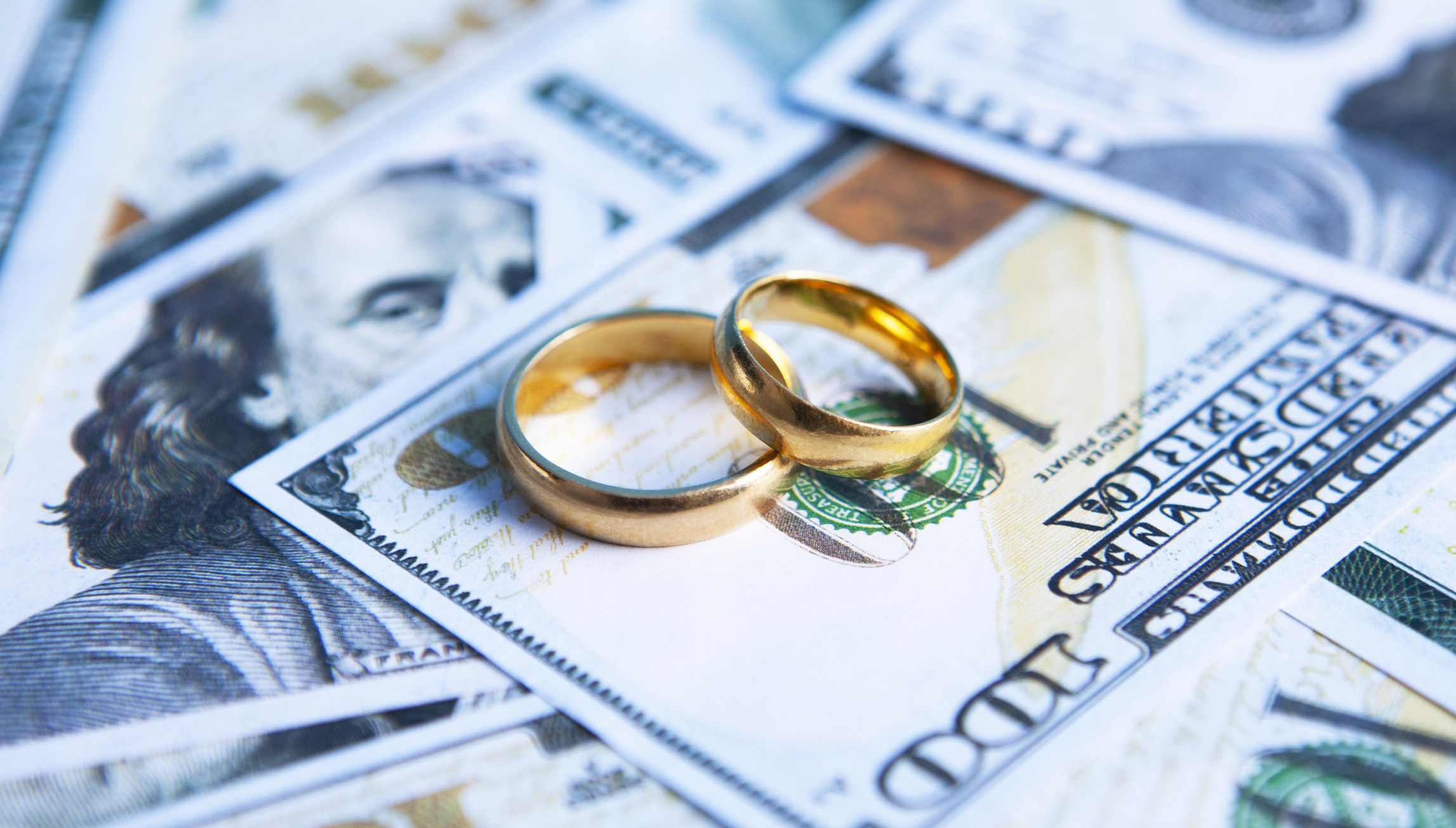 Two wedding bands on a pile of 100 dollar bills