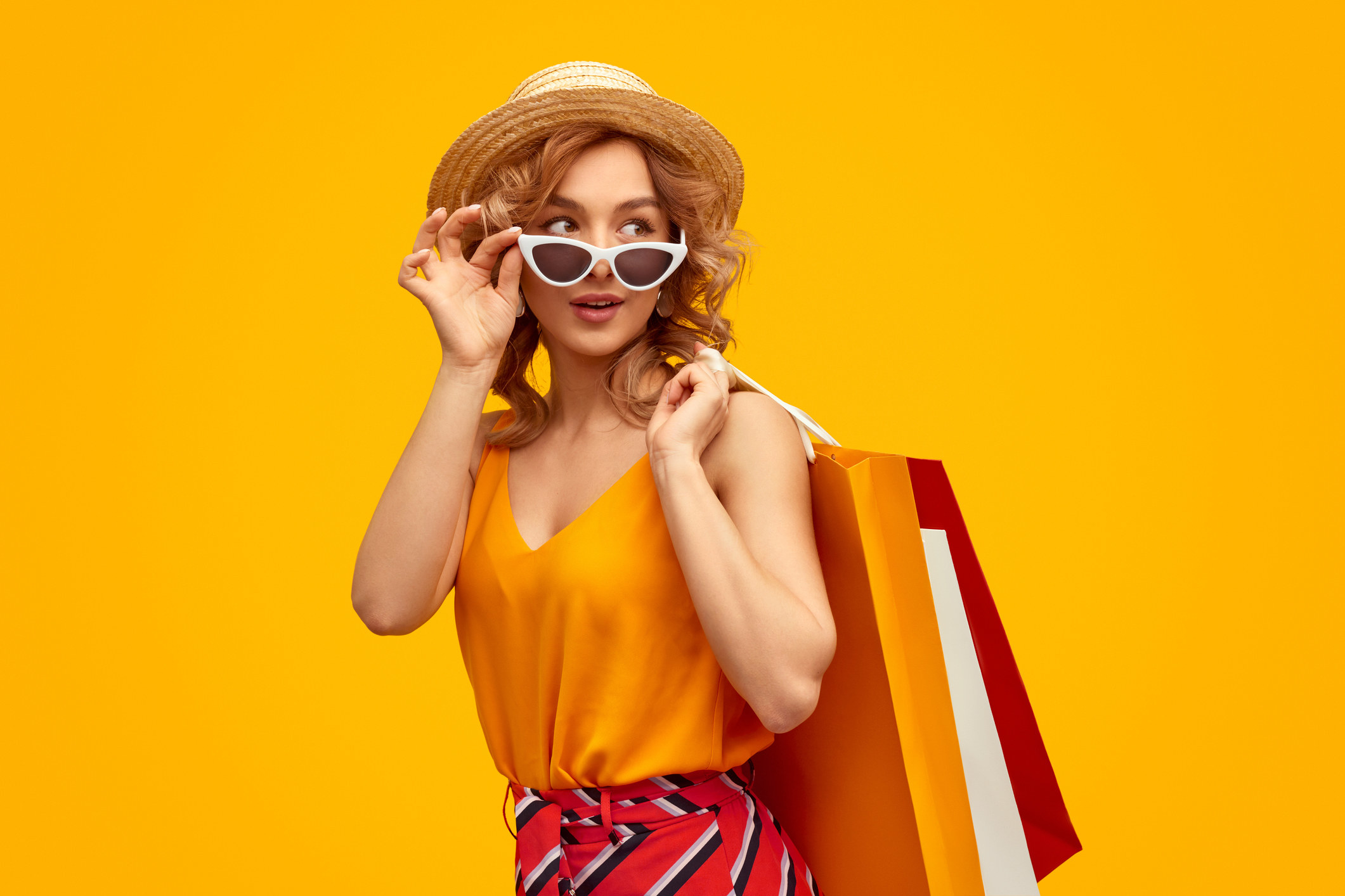 Trendy young woman with paper bags adjusting sunglasses and looking away over shoulder during shopping against bright yellow background