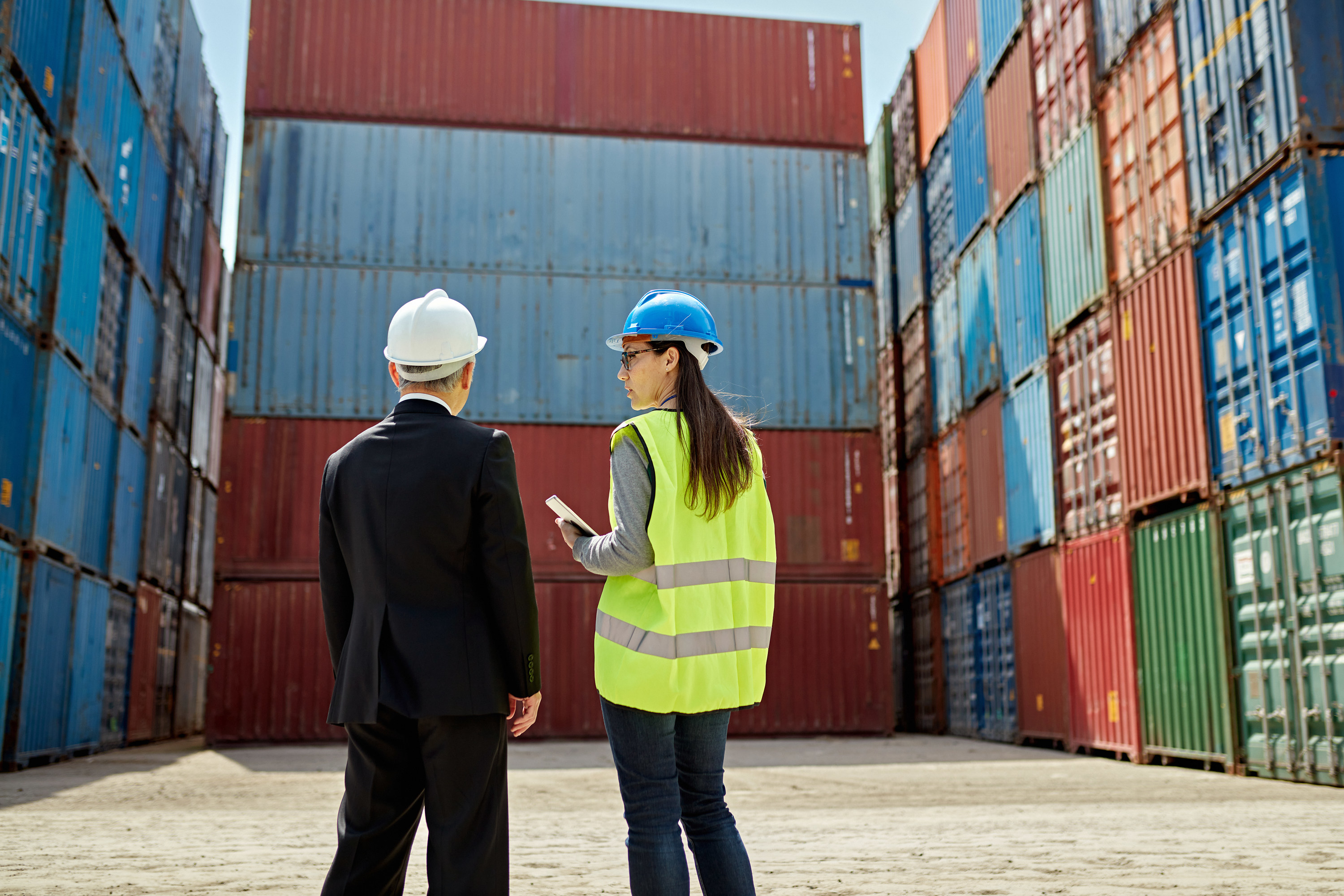 Logistics managers having a conversation in front of large shipping containers