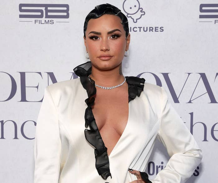 Demi rocks short hair and a white dress with a plunging neckline