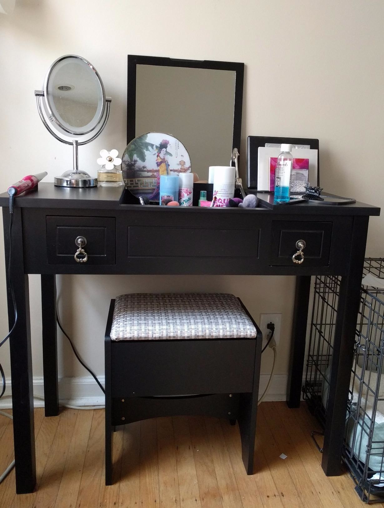 reviewer photo of a black vanity table with flip up mirror and products on top, with a stool tucked underneath