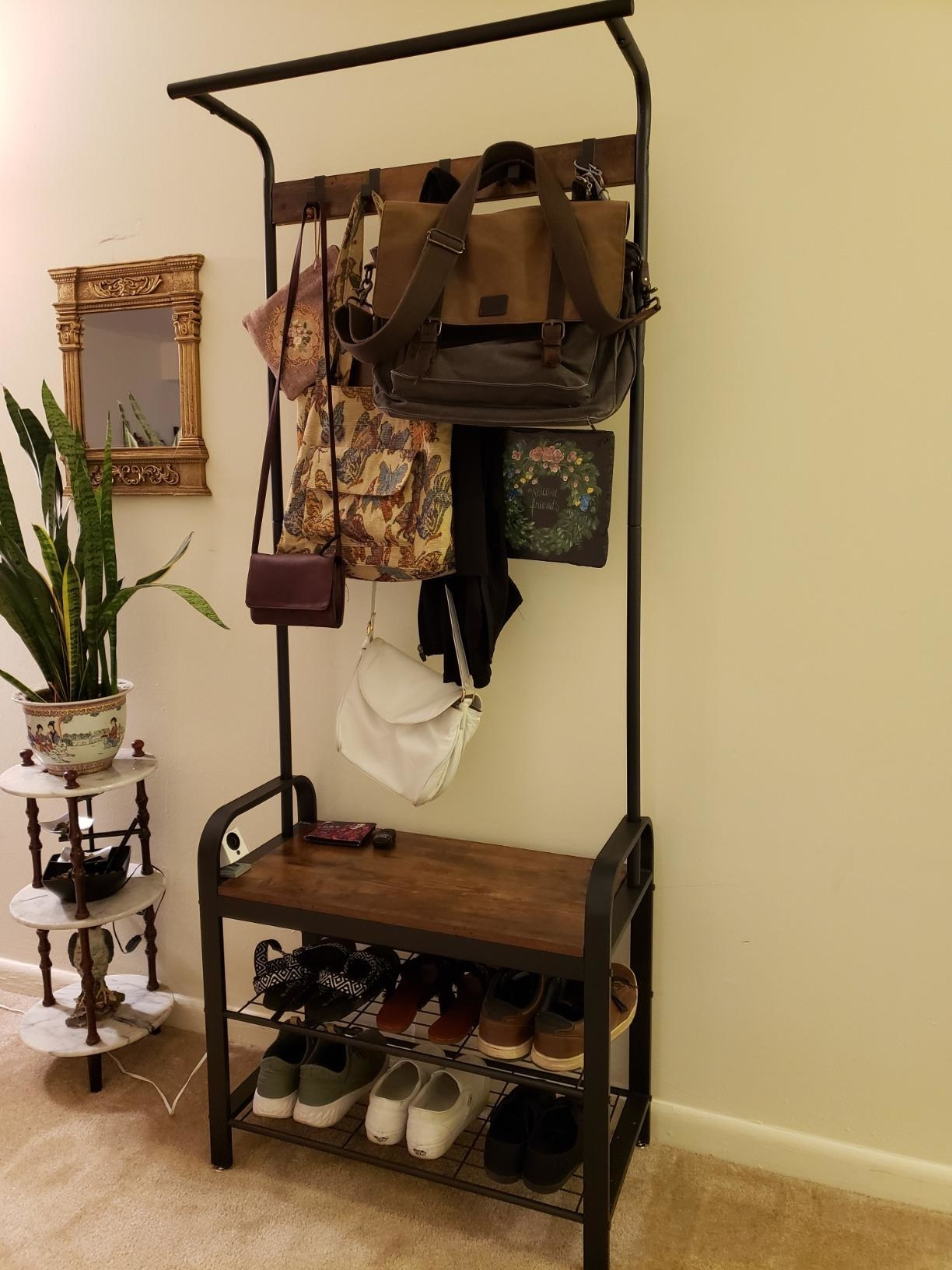reviewer photo of a coat rack with bags hanging on the racks and shoes on the shelves