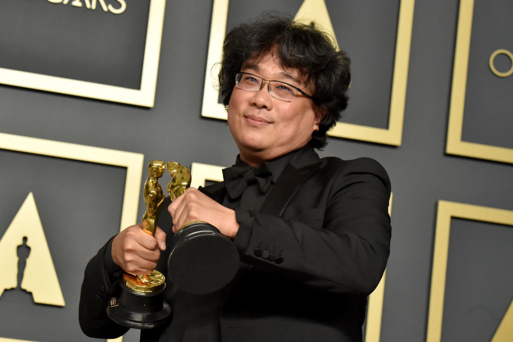 Parasite director Bong Joon-ho holding two of his four Oscar awards and making them kiss
