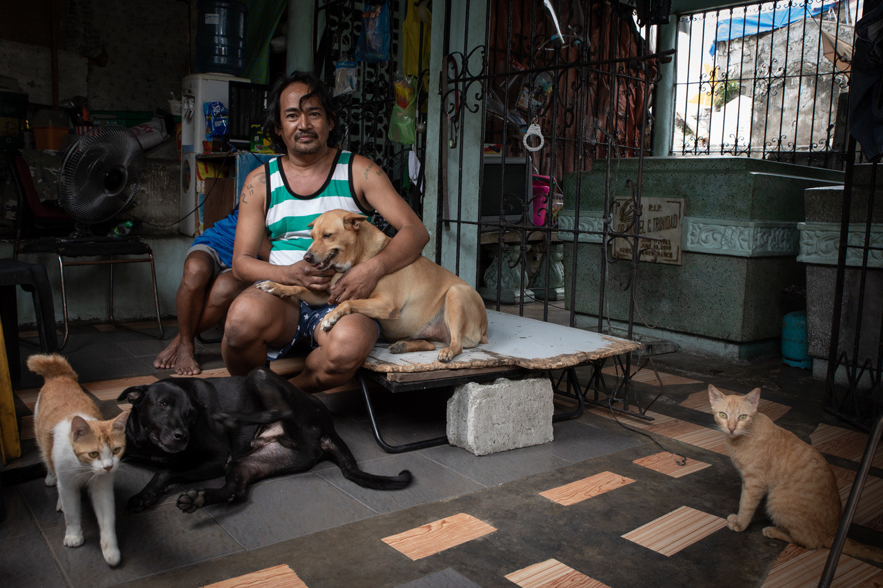 A man with two dogs and two cats sits on a cot in a graveyard in the Philippines
