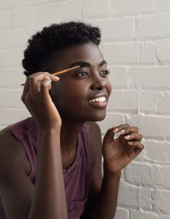 A model using a spoolie brush to apply oil to their eyebrows