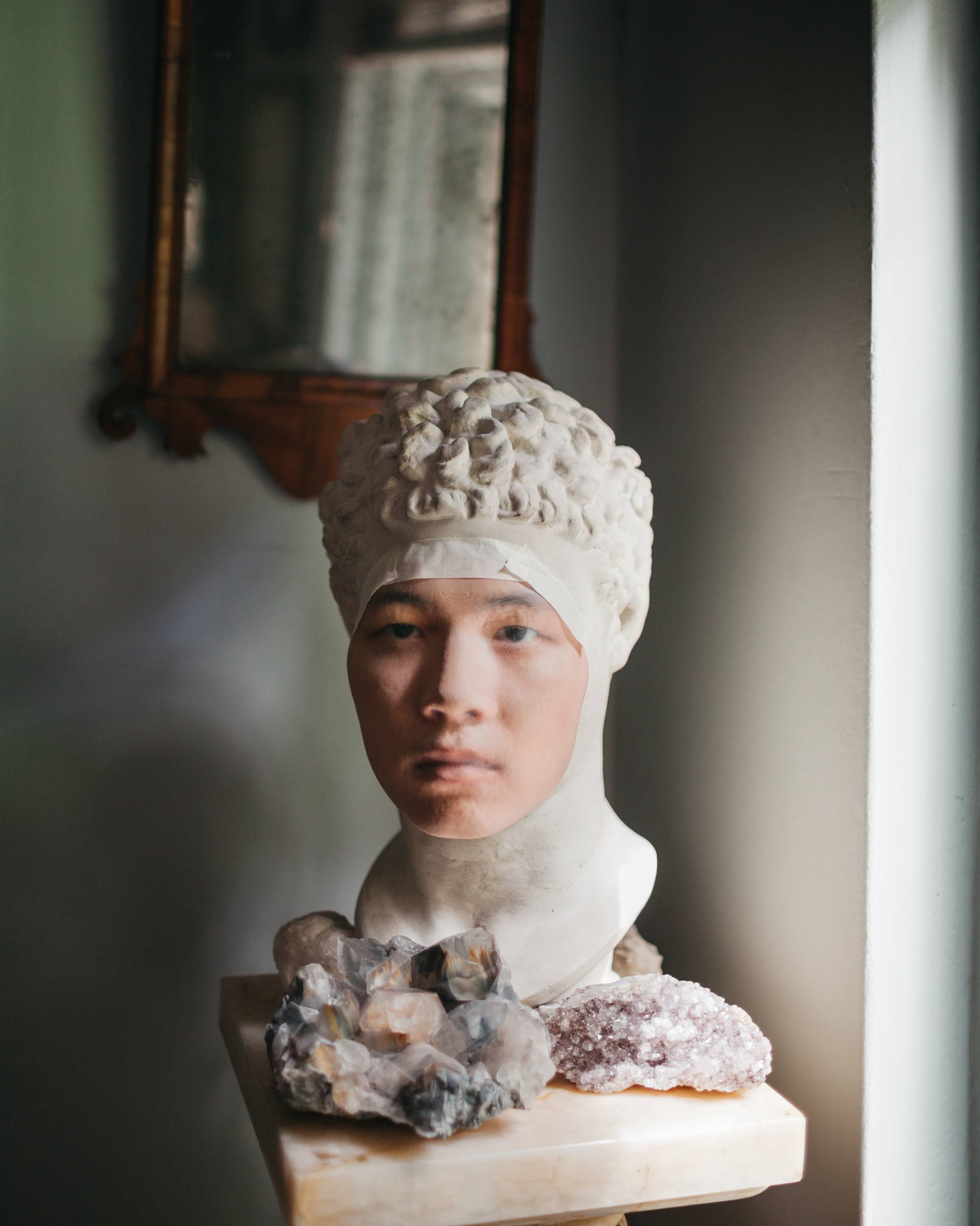 A mans face taped to a bust statue with crystals around it on a pedestal