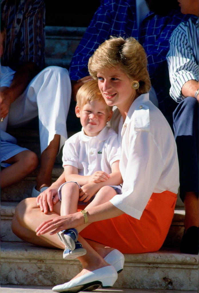 Princess Diana holding a young Harry in her arms as they sit on some steps