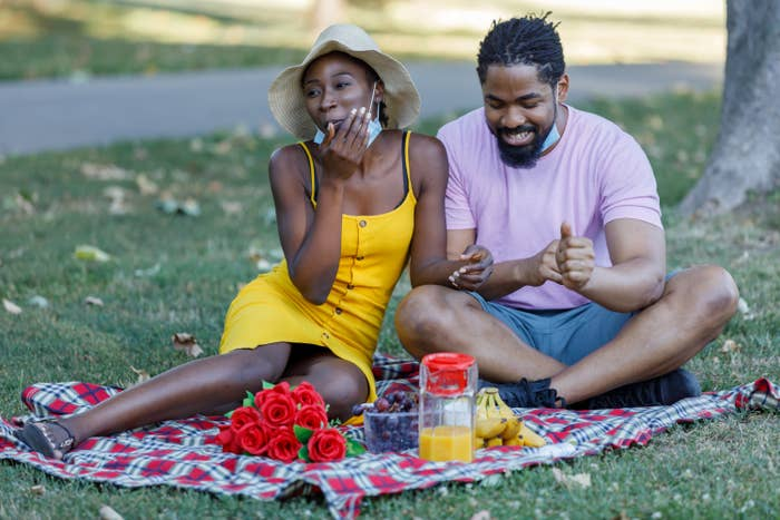 Two people on a date sit on a picnic blanket in a park