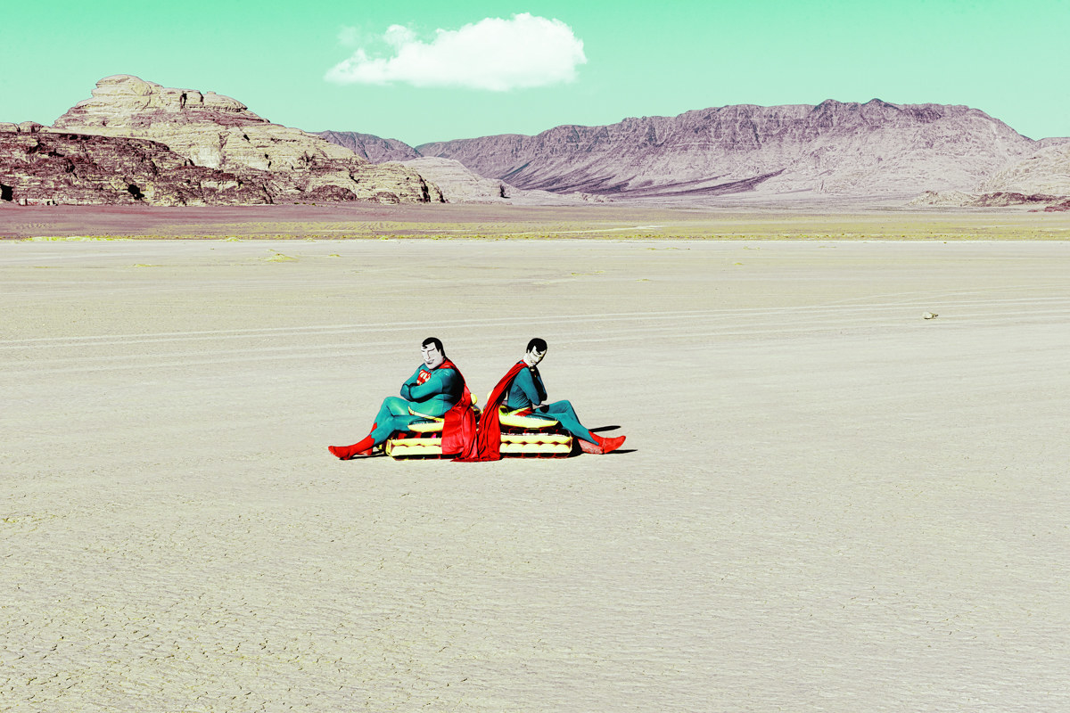 Two men dressed as superman sitting with their backs to each other in a desert landscape