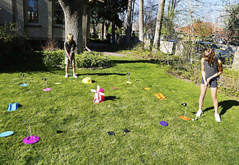 two model kids playing with the golf set outside