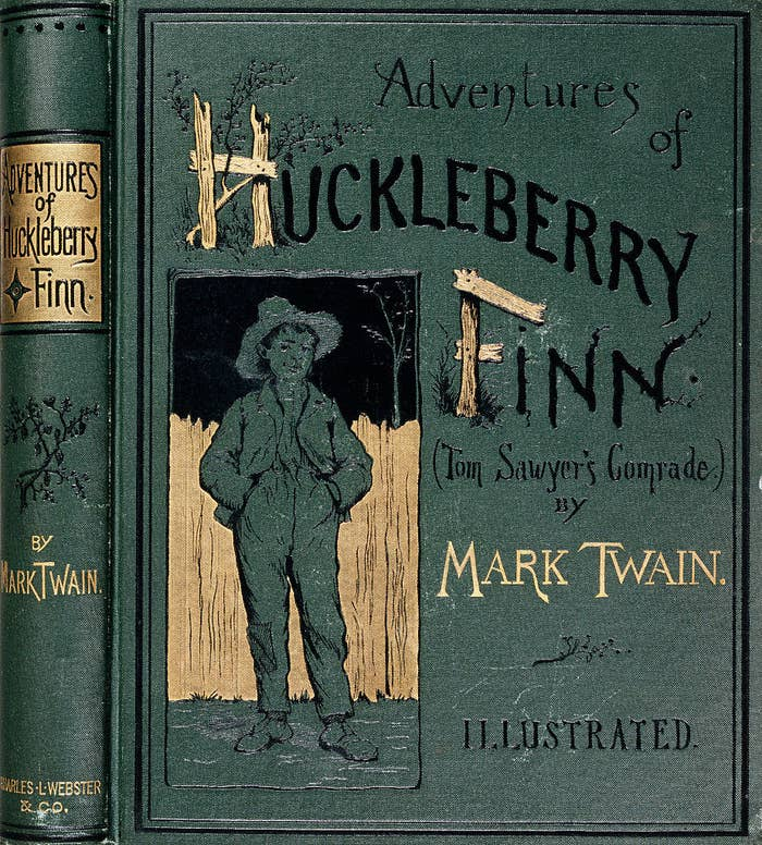 A young boy wearing bagging clothes with his hands in his pockets on the book cover of The Adventures of Huckleberry Finn