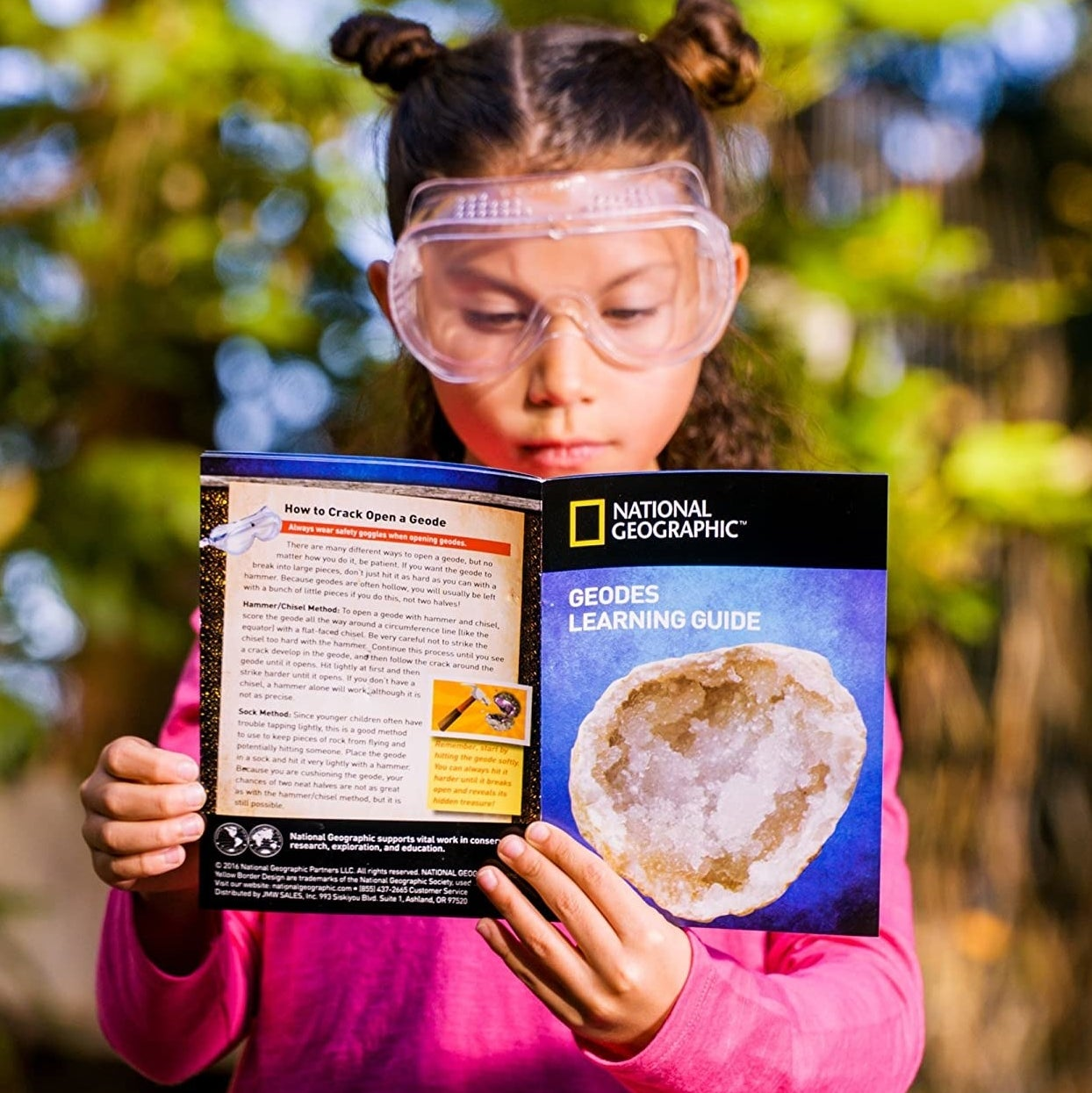 a model holding the national geographic geode book