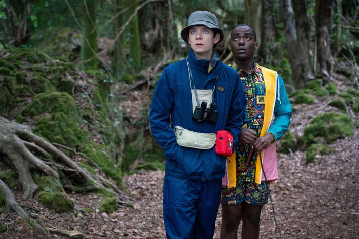 Asa Butterfield and Ncuti Gatwa stand in the woods