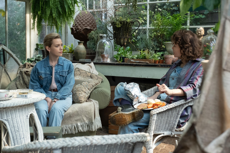 Victoria Pedretti and Amelia Eve sit in a greenhouse