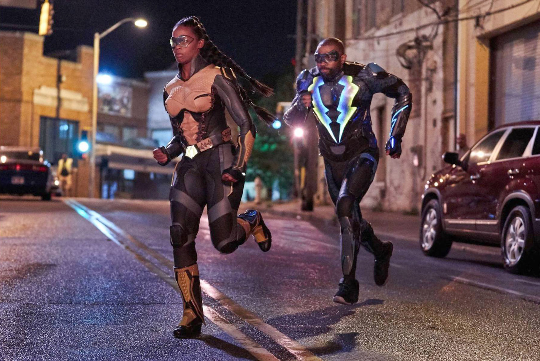 Nafessa Williams and Cress Williams run in supersuits.