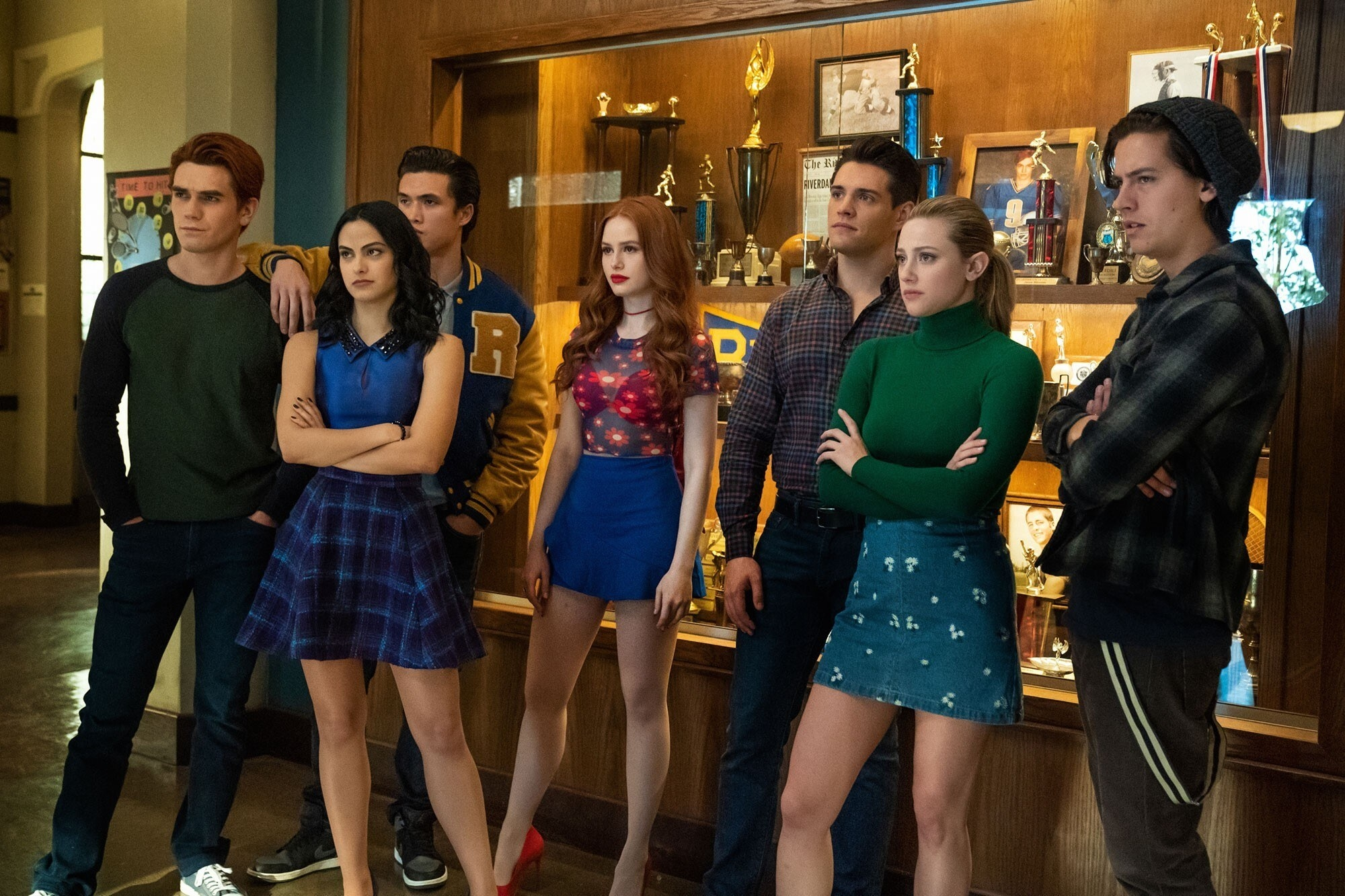 KJ Apa, Camila Mendes, Charles Melton, Madelaine Petsch, Casey Cott, Lili Reinhart, and Cole Sprouse stand in front of a trophy case