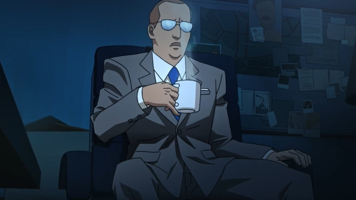 man in a suit and glasses drinking coffee