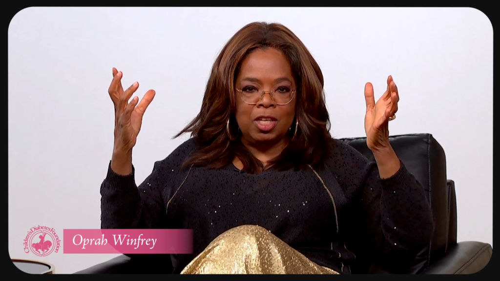 Oprah sitting in a chair and speaking
