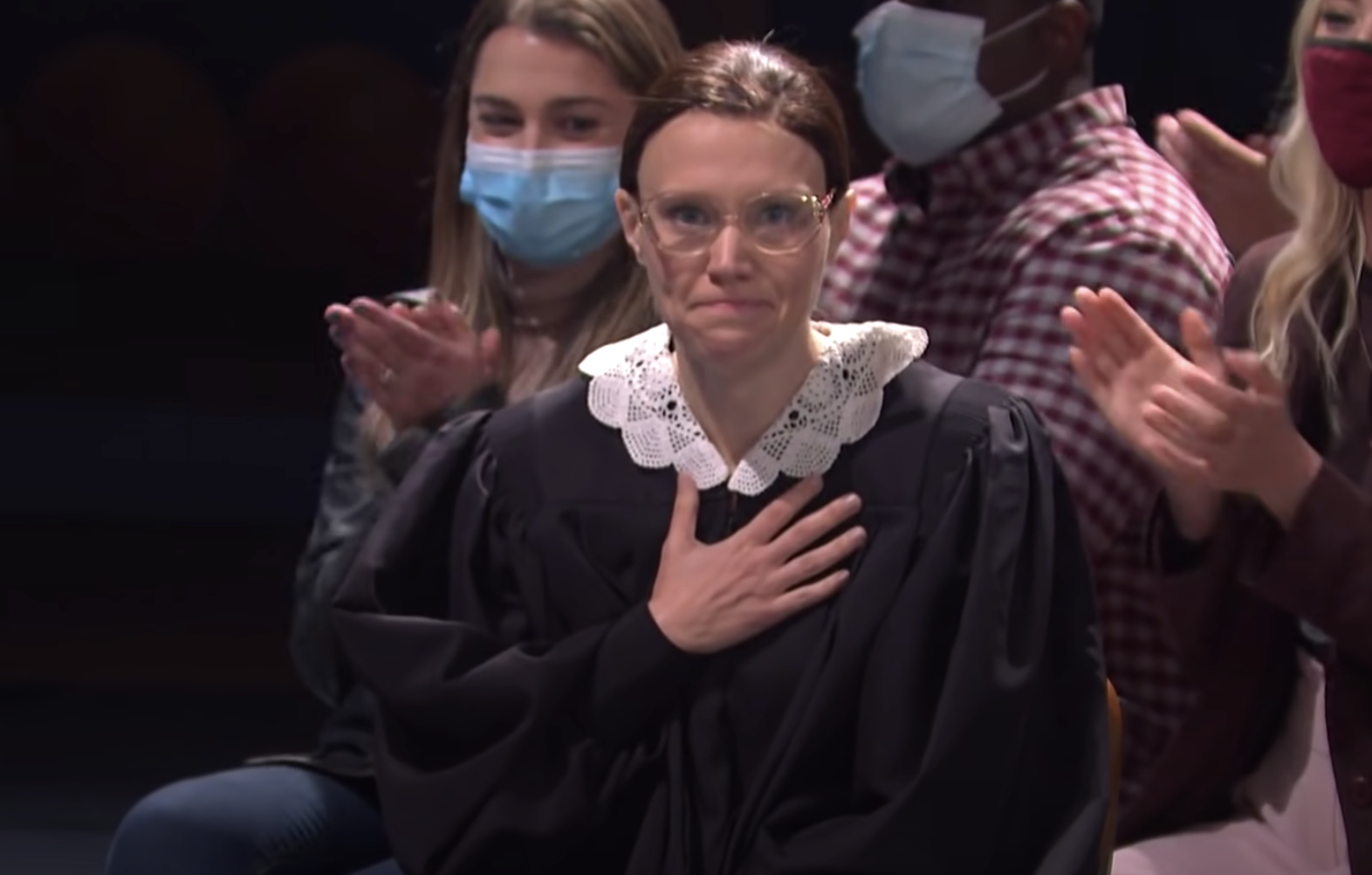 Kate McKinnon dressed as a justice, with her right hand on her heart