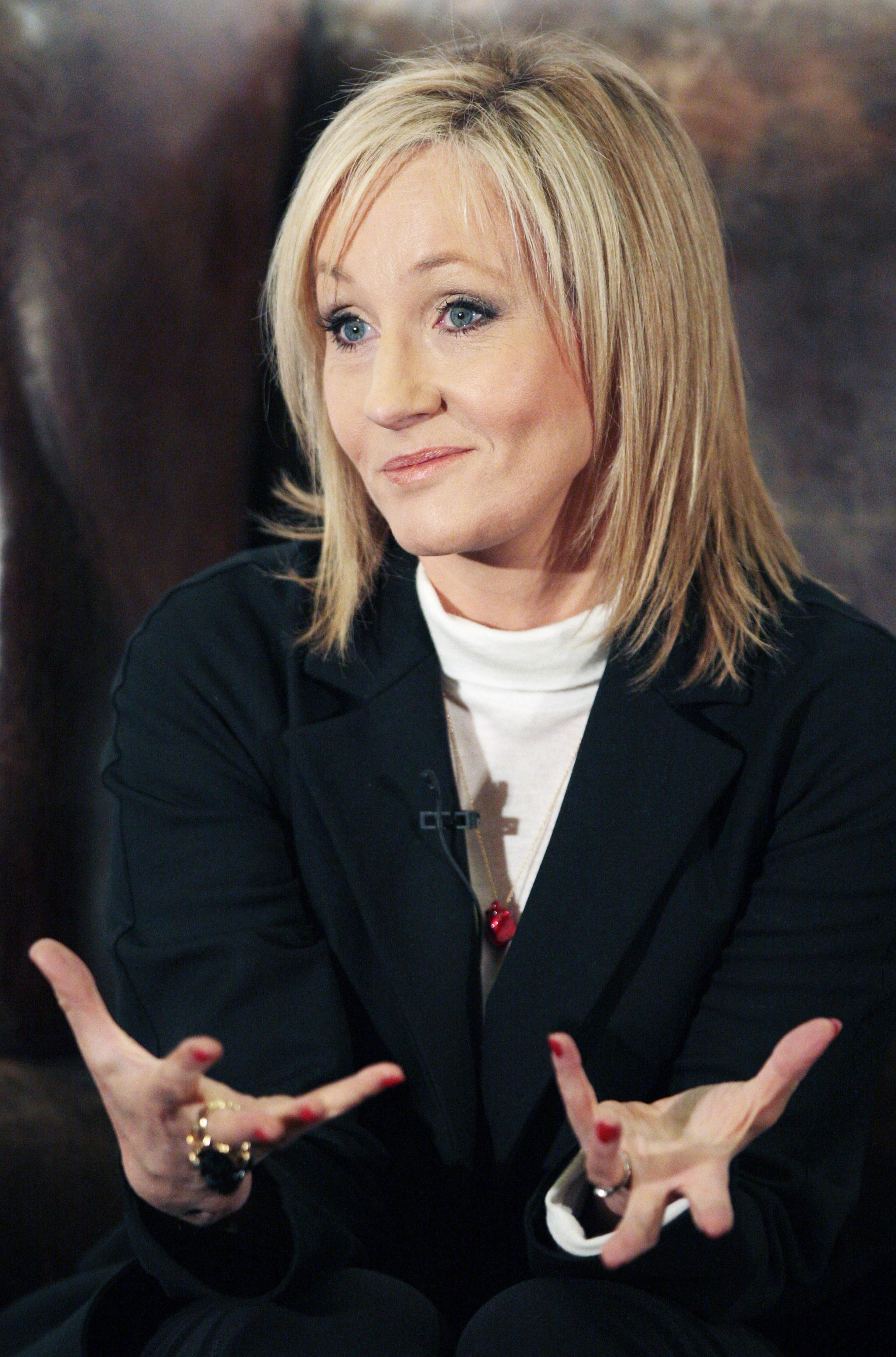 J.K. Rowling with her hands raised with palms up