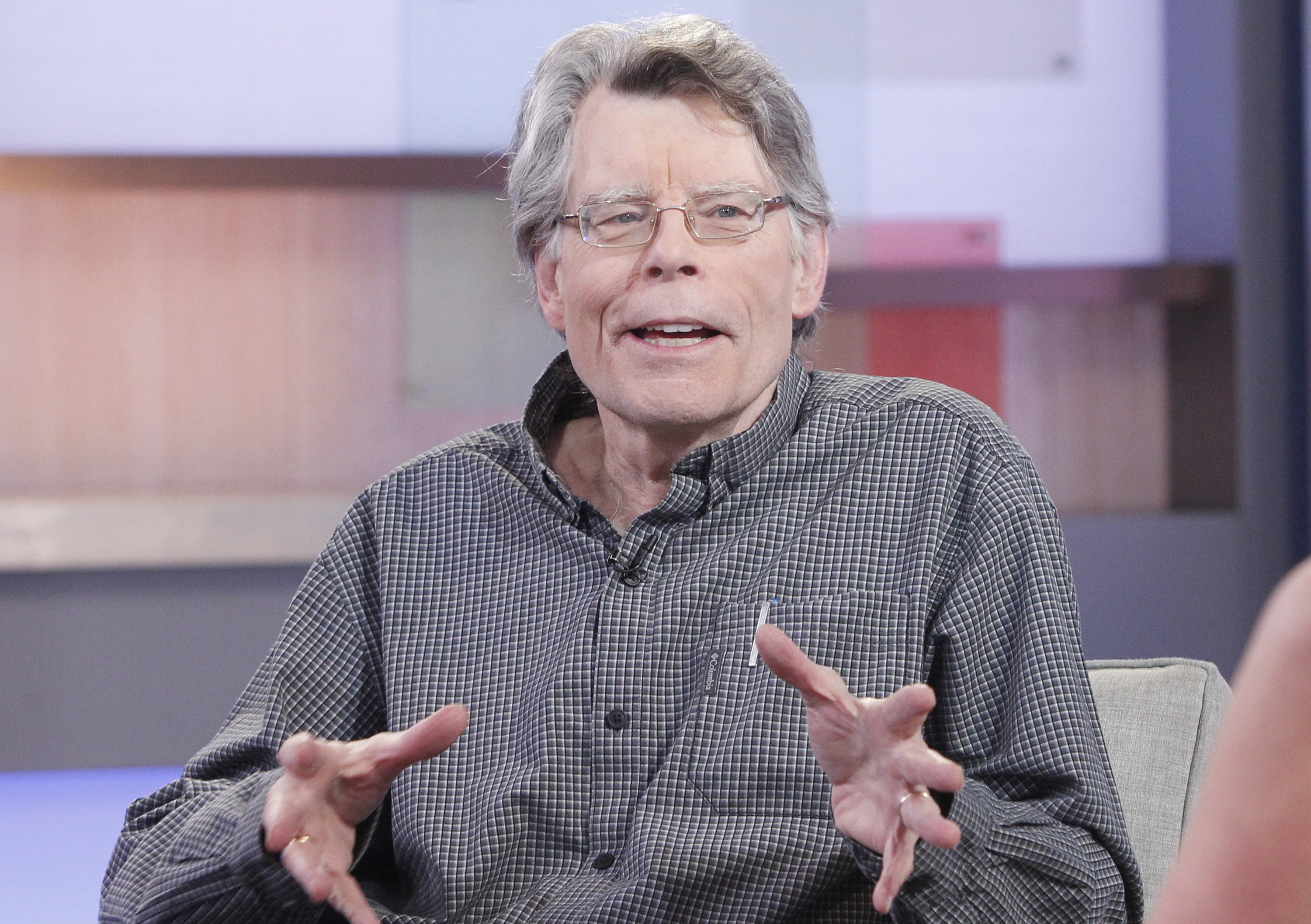 Stephen King talking to someone while sitting and gesturing with his hands