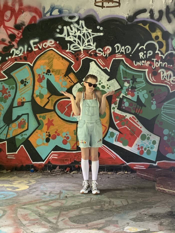 A trans person shrugs before a background of graffiti