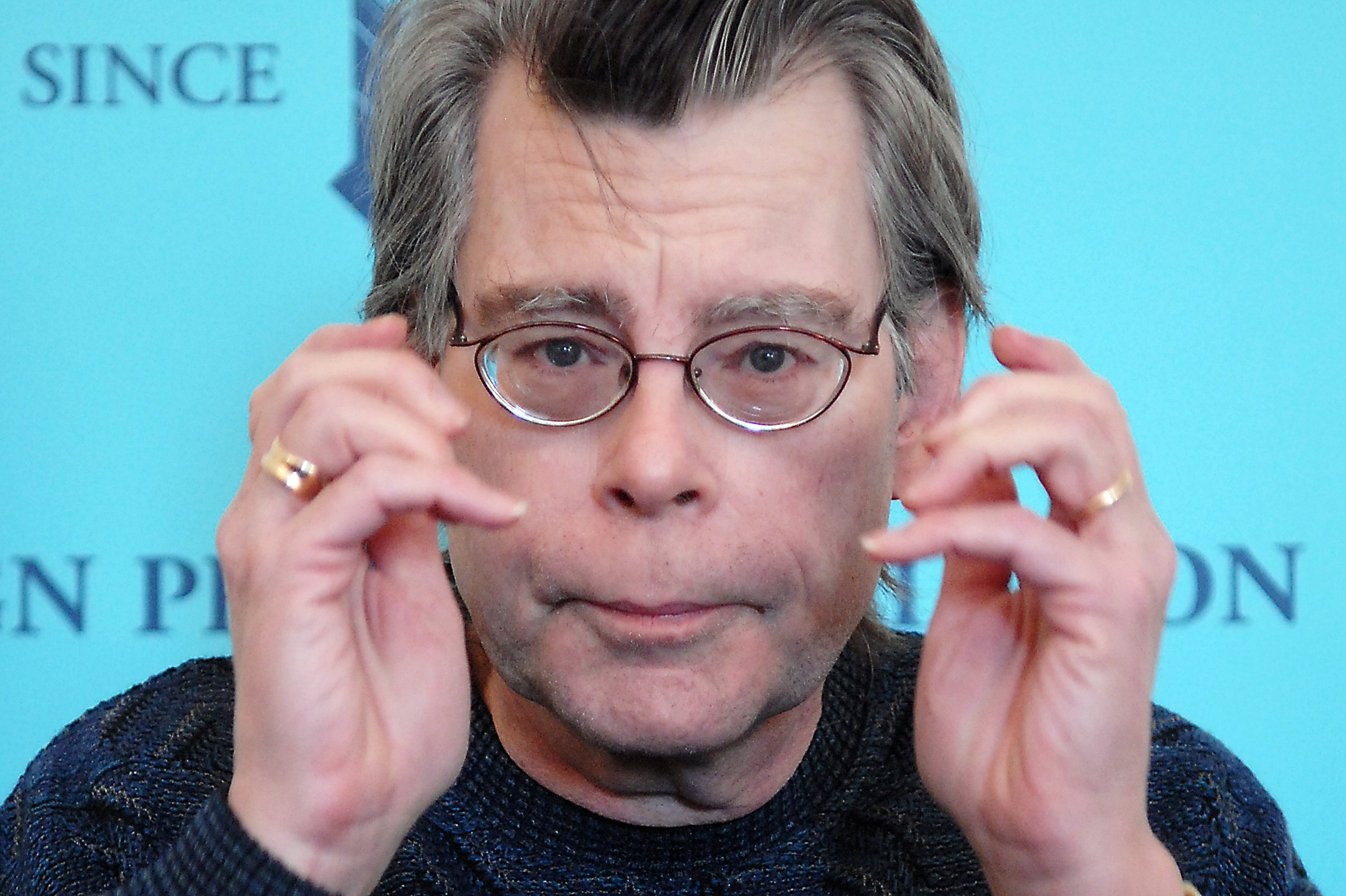Stephen King holding his hands up near his face