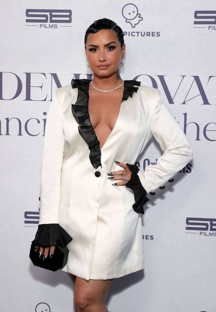 Demi Lovato on the red carpet, wearing a long-sleeved, short coatdress