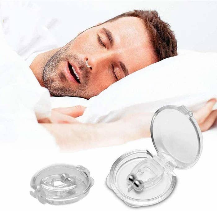 A person sleeping with the anti-snore clip in their nose.