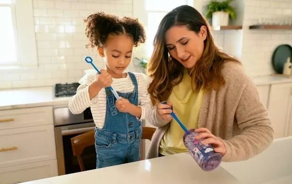 A parent and child cleaning a water bottle and straw