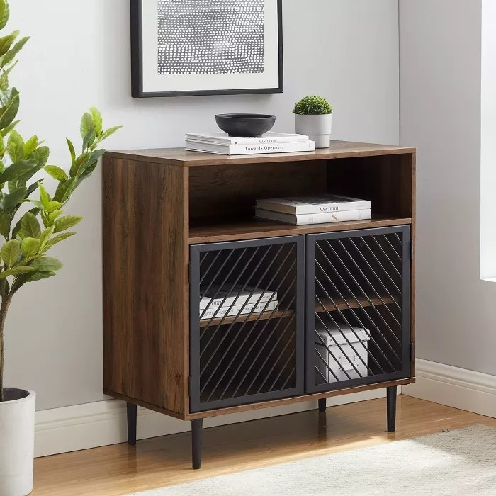 The wooden cabinet with metal doors and legs